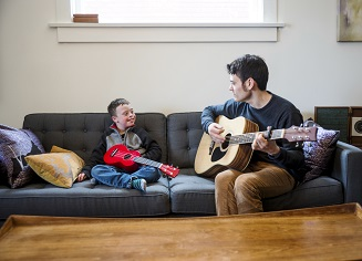 A cute boy with Downs Syndrome having fun playing guitar with his dad on the couch at home. he is holding a red ukulele and his dad is strumming an acoustic guitar and singing.